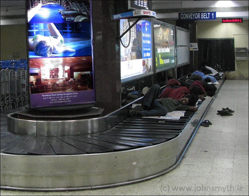 Baggage handlers resting between shifts at Bangalore's Hindustan airport, in India