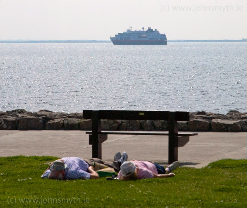Sunbathers on Salthill Prom with cruise ship in the background in Galway Bay